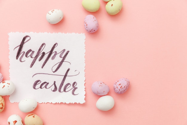 Happy easter concept. inscription happy easter letters candy chocolate eggs and jellybean sweets isolated on trendy pastel pink background. simple minimalism flat lay top view copy space.