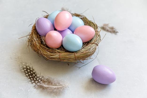 Счастливой пасхи концепции. подготовка к празднику. красочно оформленные пасхальные яйца в гнезде с пером на сером фоне бетонного камня