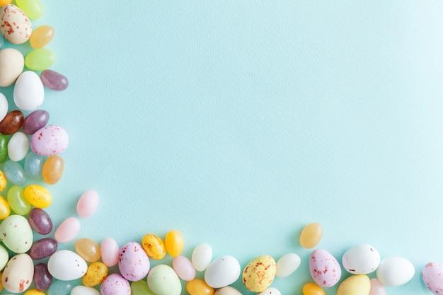 ハッピーイースターのコンセプトです。休日の準備。イースターキャンディチョコレートの卵とトレンディなパステルブルーの背景に分離されたジェリービーンズのお菓子。シンプルなミニマリズムフラットレイアウトトップビューコピースペース。