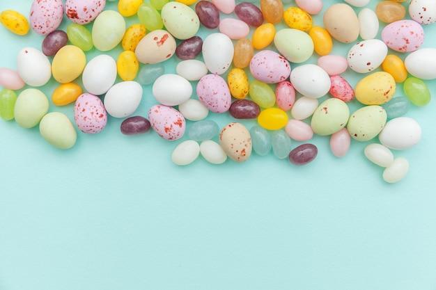 ハッピーイースターのコンセプト。休日の準備。トレンディなパステルブルーの背景に分離されたイースターキャンディチョコレートの卵とジェリービーンズのお菓子
