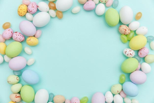 ハッピーイースターのコンセプトです。休日の準備。イースターキャンディチョコレートの卵とトレンディなパステルブルーに分離されたジェリービーンズのお菓子。シンプルなミニマリズムフラットレイアウトトップビューコピースペース。