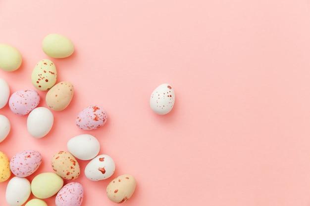 ハッピーイースターのコンセプトです。休日の準備。イースターキャンディチョコレートの卵とトレンディなパステルピンクの背景に分離されたジェリービーンズのお菓子。シンプルなミニマリズムフラットレイアウトトップビューコピースペース。