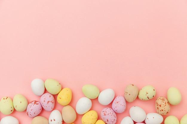 ハッピーイースターのコンセプト。休日の準備。イースターキャンディチョコレートの卵とトレンディなパステルピンクの背景に分離されたジェリービーンズのお菓子。シンプルなミニマリズムフラットレイアウトトップビューコピースペース
