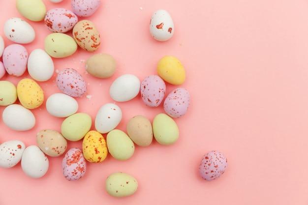 ハッピーイースターのコンセプト。休日の準備。イースターキャンディチョコレートの卵とトレンディなパステルピンクの背景に分離されたジェリービーンズのお菓子。