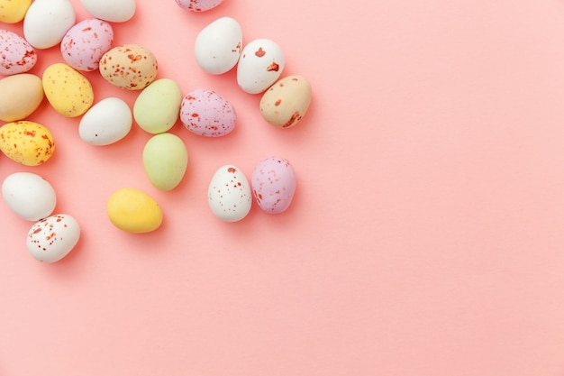 ハッピーイースターのコンセプトです。休日の準備。イースターキャンディチョコレートの卵とトレンディなパステルピンクに分離されたジェリービーンズのお菓子。シンプルなミニマリズムフラットレイアウトトップビューコピースペース。
