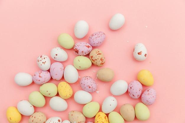 ハッピーイースターのコンセプトです。休日の準備。イースターキャンディチョコレートの卵とトレンディなパステルピンクの表面に分離されたジェリービーンズのお菓子。シンプルなミニマリズムフラットレイアウトトップビューコピースペース。