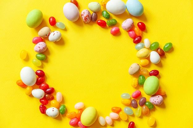 ハッピーイースターのコンセプトです。休日の準備。イースターキャンディチョコレートの卵とトレンディな黄色の背景に分離されたジェリービーンズのお菓子。シンプルなミニマリズムフラットレイアウトトップビューコピースペース。