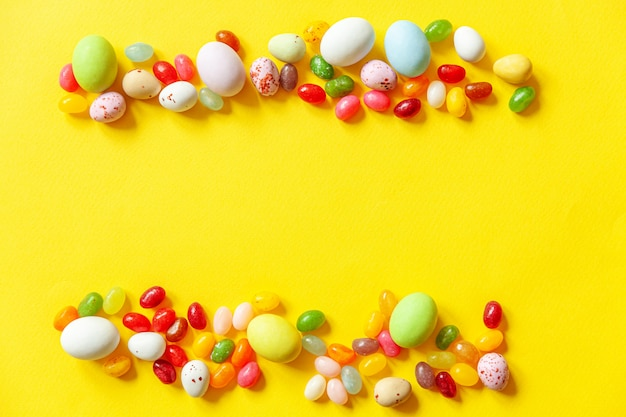 ハッピーイースターのコンセプトです。休日の準備。イースターキャンディチョコレートの卵とトレンディな黄色の背景に分離されたジェリービーンズのお菓子。