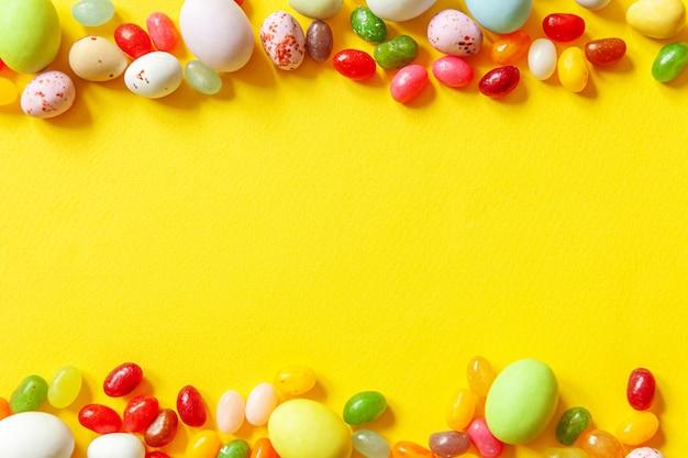 ハッピーイースターのコンセプトです。休日の準備。イースターキャンディチョコレートの卵とトレンディな黄色に分離されたジェリービーンズのお菓子。シンプルなミニマリズムフラットレイアウトトップビューコピースペース。