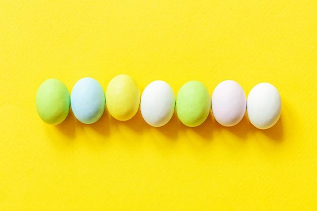 ハッピーイースターのコンセプトです。休日の準備。イースターキャンディチョコレートの卵のカラフルなパステルのお菓子とトレンディな黄色の背景に分離されたバニーグッズ。シンプルなミニマリズムフラットレイアウトトップビューコピースペース。