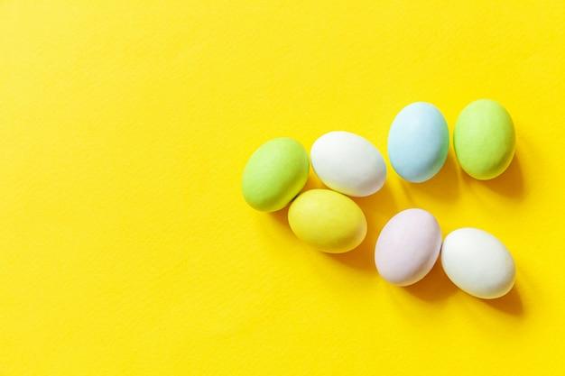 ハッピーイースターのコンセプトです。休日の準備。イースターキャンディチョコレートの卵のカラフルなパステルのお菓子とトレンディな黄色の背景に分離されたバニーグッズ。 。