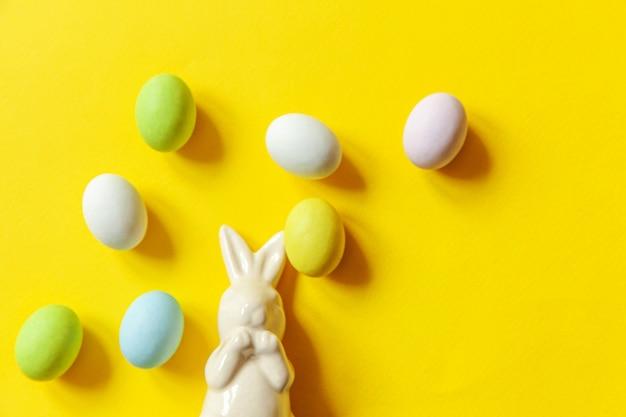 ハッピーイースターのコンセプトです。休日の準備。イースターキャンディチョコレートの卵のお菓子とトレンディな黄色の背景に分離されたバニーグッズ。