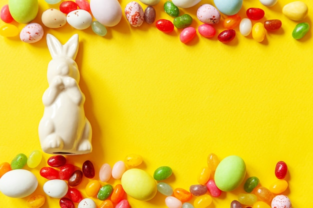 Happy easter concept. preparation for holiday. easter candy chocolate eggs bunny and jellybean sweets isolated on trendy yellow. simple minimalism flat lay top view copy space.