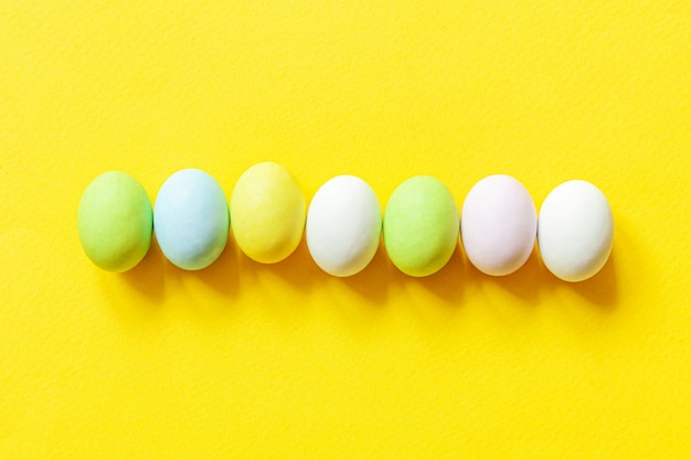 Happy easter concept. preparation for holiday. easter candy chocolate eggs colorful pastel sweets and bunny toy isolated on trendy yellow background. simple minimalism flat lay top view copy space.
