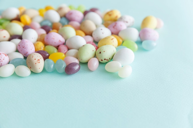 Happy easter concept. preparation for holiday. easter candy chocolate eggs and jellybean sweets isolated on trendy pastel blue. simple minimalism flat lay top view copy space.
