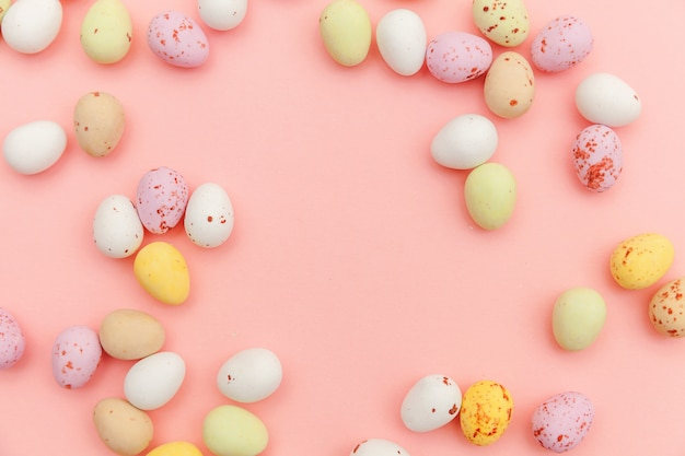 Happy easter concept. preparation for holiday. easter candy chocolate eggs and jellybean sweets isolated on trendy pastel pink background. simple minimalism flat lay top view copy space.