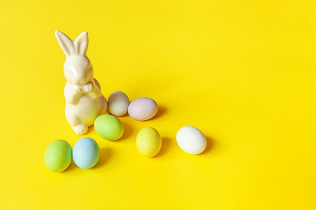 Happy easter concept. preparation for holiday. easter candy chocolate eggs sweets and bunny toy isolated on trendy yellow. simple minimalism copy space.