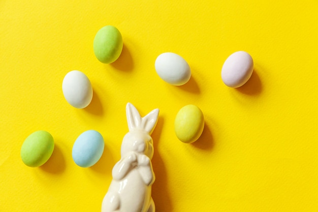 Happy easter concept. preparation for holiday. easter candy chocolate eggs sweets and bunny toy isolated on trendy yellow. simple minimalism flat lay top view copy space.