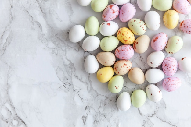 Happy easter concept. preparation for holiday. easter pastel candy chocolate eggs sweets on trendy gray marble background. simple minimalism flat lay top view copy space.