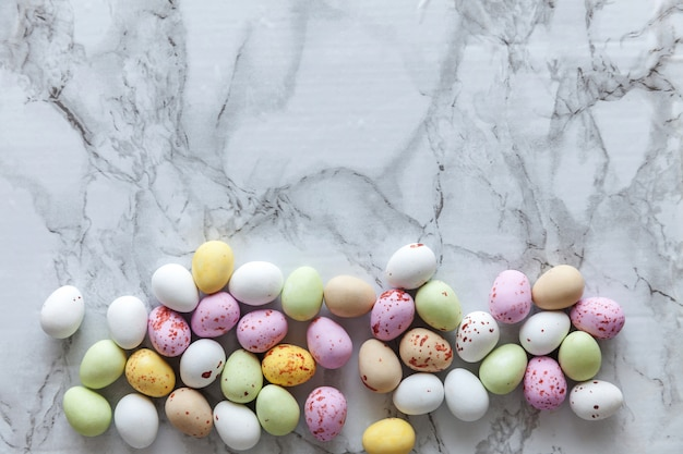 Happy easter concept. preparation for holiday. easter pastel candy chocolate eggs sweets on trendy gray marble. simple minimalism flat lay top view copy space.