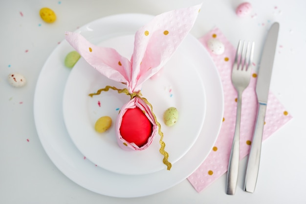 Happy easter concept - top view of easter egg wrapped in pink napkin shaped like bunny ears