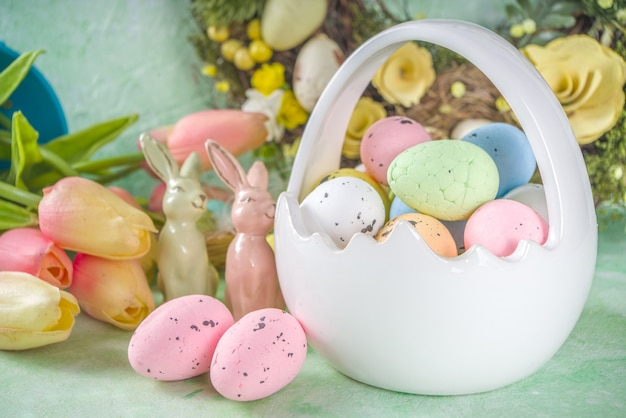 Happy easter concept with easter eggs in basket and spring flowers. easter background with copy space and photo frame