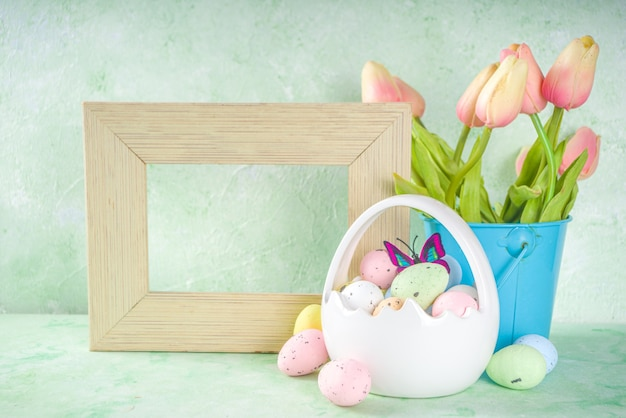 バスケットと春の花のイースターエッグとハッピーイースターのコンセプト。コピースペースとフォトフレームとイースターの背景