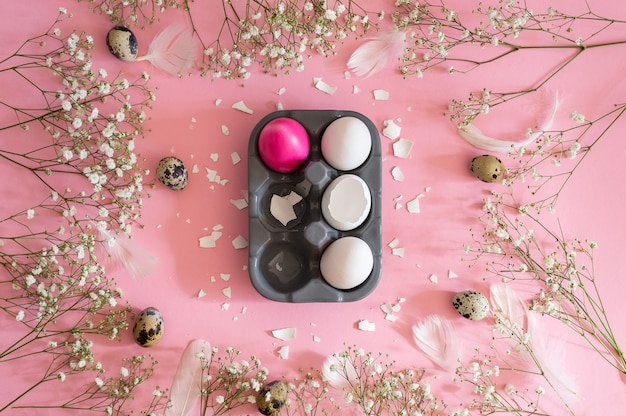Happy easter. congratulatory easter background. easter eggs with spring flowers gypsophila on a pink background. holiday concept