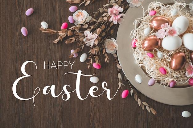 Хв. поздравительная пасха. пасхальные яйца на металлической пластине с весенними цветами на деревянном фоне. концепция праздника