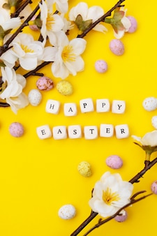 Happy easter. cubes with text on yellow background. spring brunches with white flowers and candy, chocolate easter eggs. minimalistic flat lay.