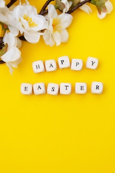 Happy easter. cubes with text on yellow background. spring brunches with white flowers. minimalistic flat lay.