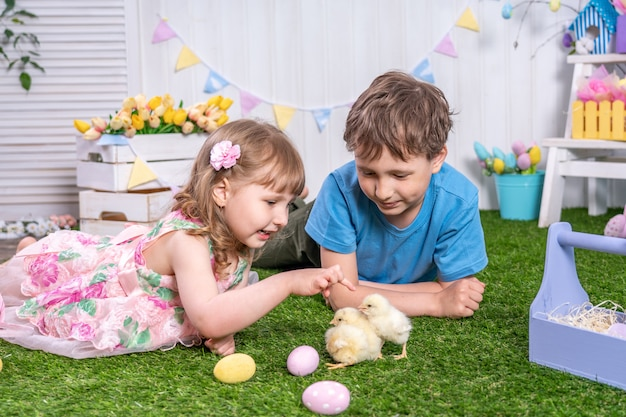 Happy easter! cute children lying on grass with eggs and petting little chicks