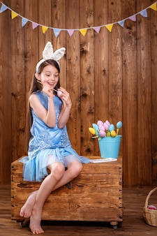 Happy easter! cute girl sitting on a wooden chest and coloring an easter egg.