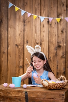 Happy easter! cute girl sitting behind wooden chest and coloring an easter egg.