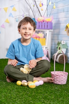 Happy easter! cute happy easter! a cheerful boy sits on grass with eggs and petting little chicks