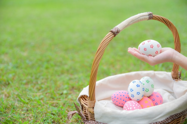 ハッピーイースターの日。緑の芝生の背景に卵狩りの後の子供たちの手でカラフルなイースターエッグ。