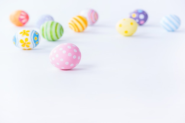 幸せなイースターの日のカラフルな卵とコピースペースで白い背景にぼやけています。