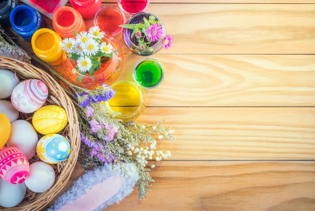 Happy easter day colorful eggs and flower a set of food coloring, acrylic paintbrush for do it yourself on brown wooden floor with copy space