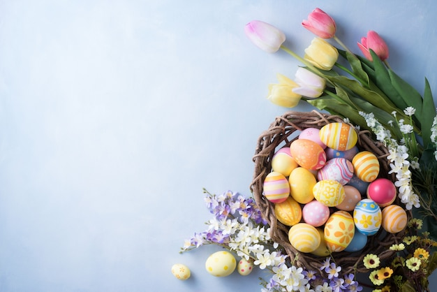 Happy easter day colorful eggs in nest and flower decoration on paper
