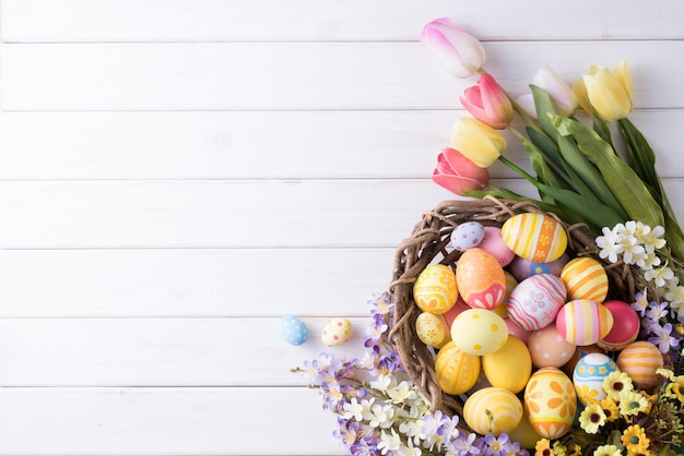 Happy easter day colorful eggs in nest and flower decoration on white wood