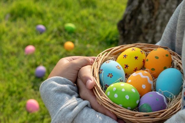 ハッピーイースターの日。イースターエッグのコンセプトです。公園でカラフルな卵を集める少年。