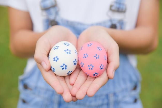 ハッピーイースターの日。イースターエッグのコンセプトです。卵狩りの後の子供の手の中のカラフルなイースターエッグ。