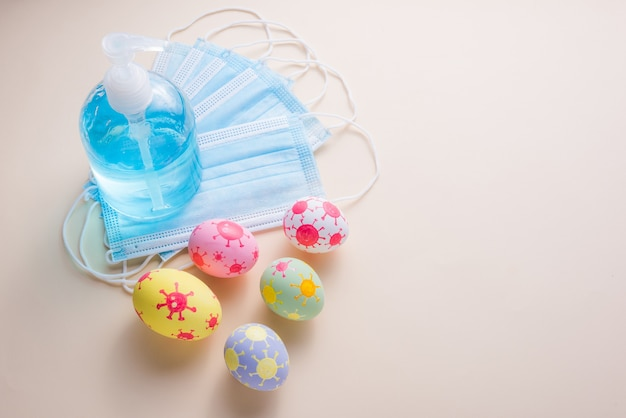 幸せなイースターの日の卵とコロナウイルス(covid-19)は、コピースペースのある紙の背景にサージカルマスクアルコールゲルを持っています。
