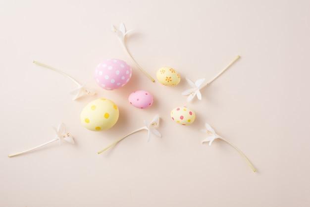幸せなイースターの日の卵とコピースペースと紙の背景に花。