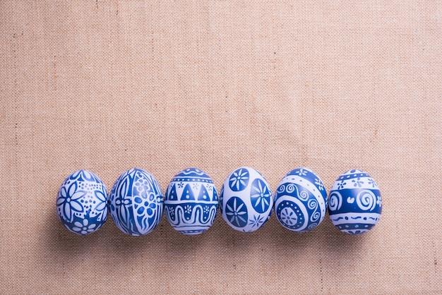 コピースペースと茶色の布の背景にハッピーイースターの日の卵。
