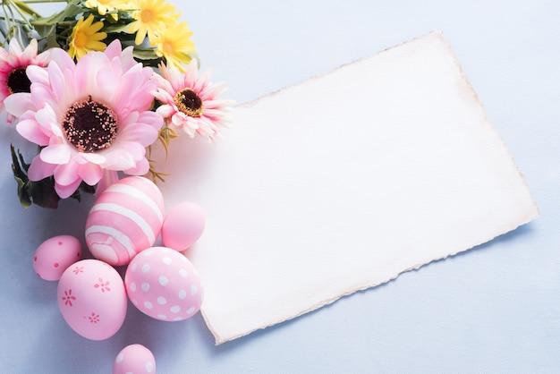 幸せなイースターの日のピンクの卵と紙の花の装飾