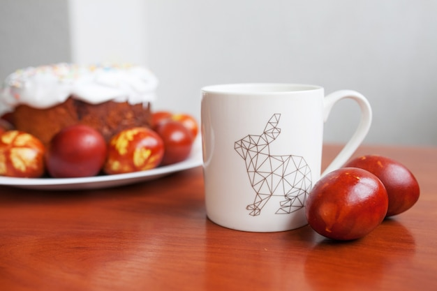 ハッピーイースターの日。イースターケーキの中でウサギのイメージと白いカップ。朝の飲み物。イースターのお祝いのコンセプト。