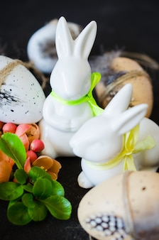 Happy easter. decorative easter eggs, rabbits and blossoming spring branch.