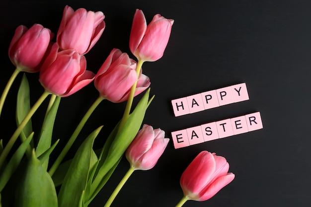 イースター、おめでとう!ピンクのチューリップとイースターの背景。春の休日のコンセプト。