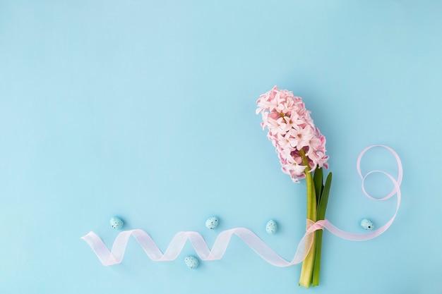 ハッピーイースター!スカイブルーの背景にあるイースターデコレーションカードは、ピンクのヒヤシンスの花、ピンクのリボン、イースターエッグです。スペースをフラットにコピーします。
